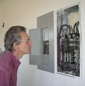 Photo of Jamey inspecting electrical panel